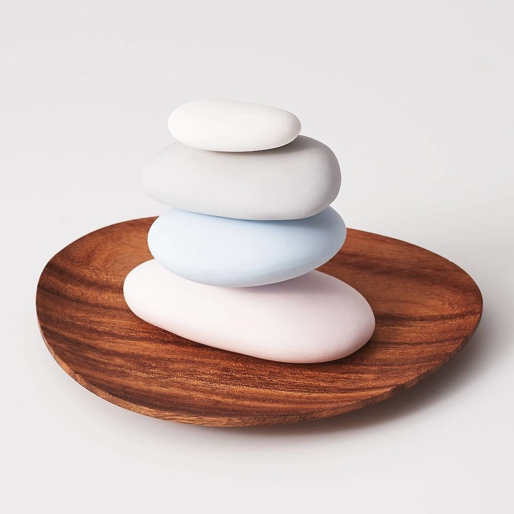 four pebbles in pastel colors on a wood plate