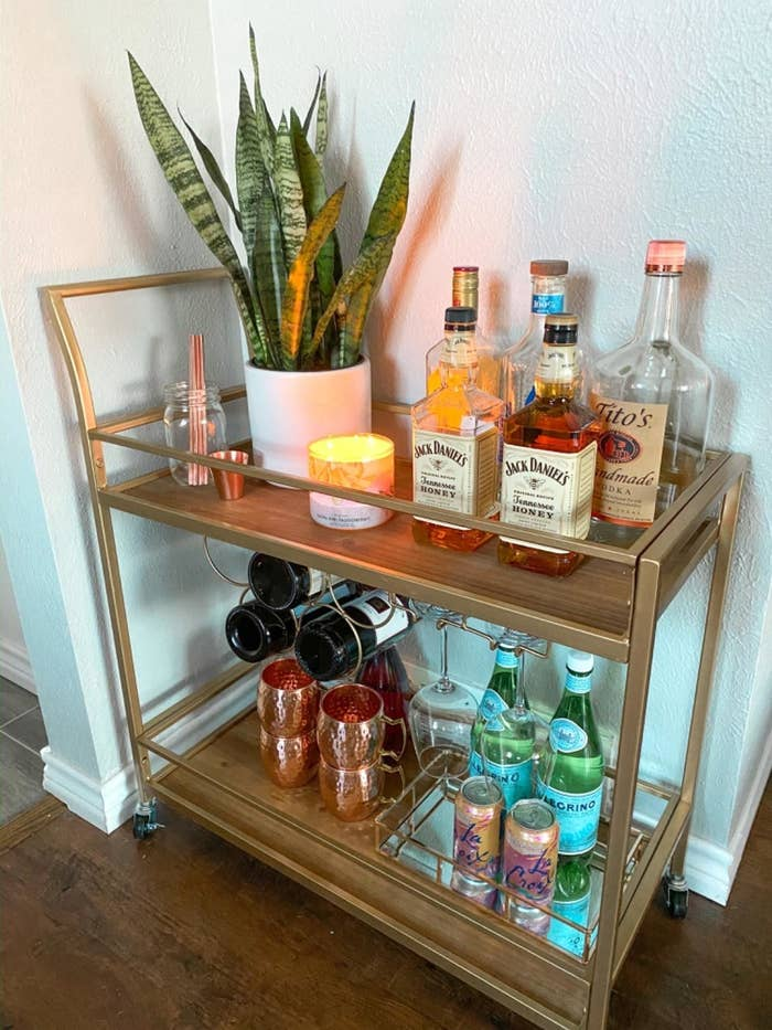 a gold two tiered bar cart on wheels