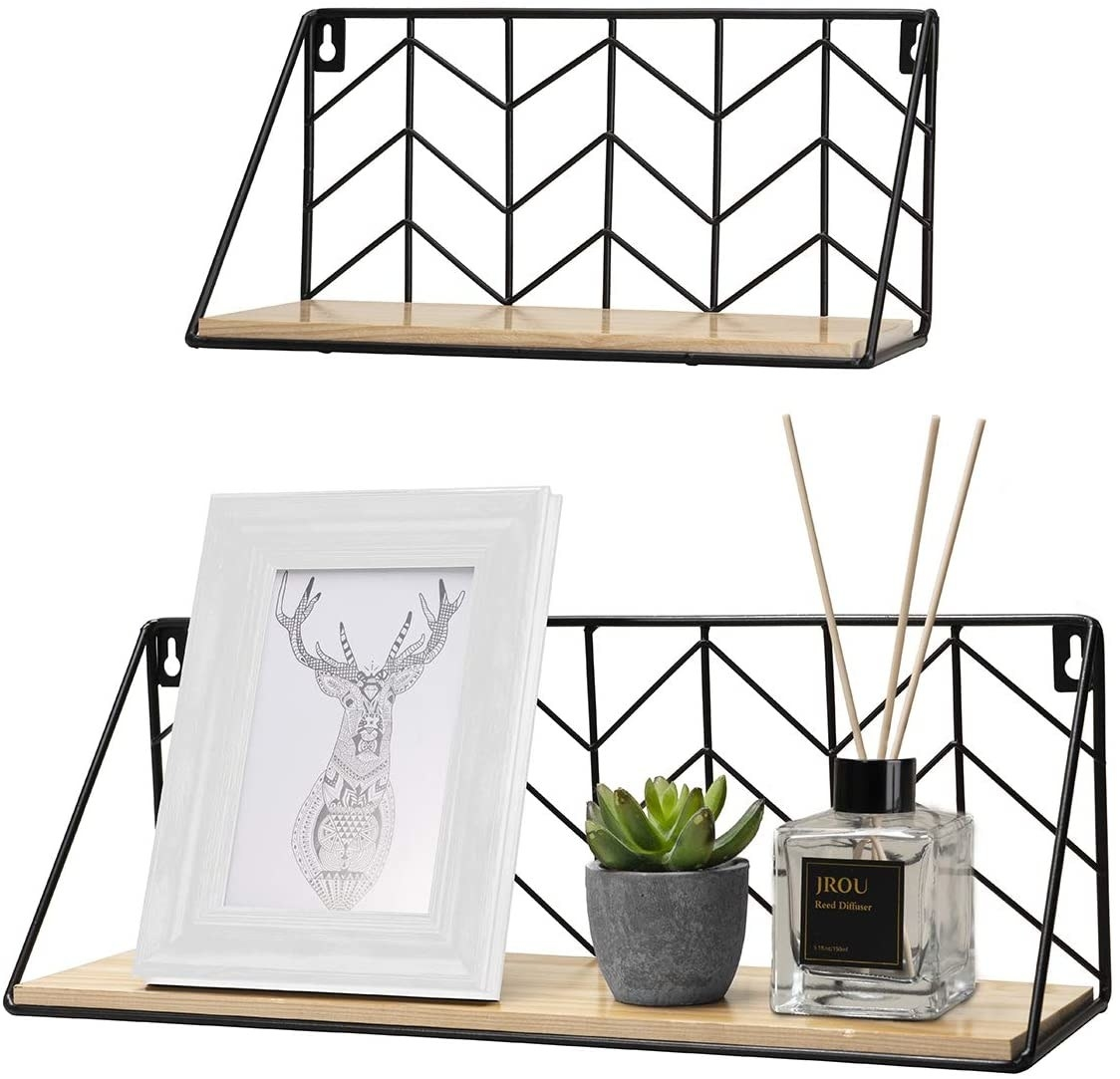 two shelves with a natural wood base and black metal backing in a chevron design