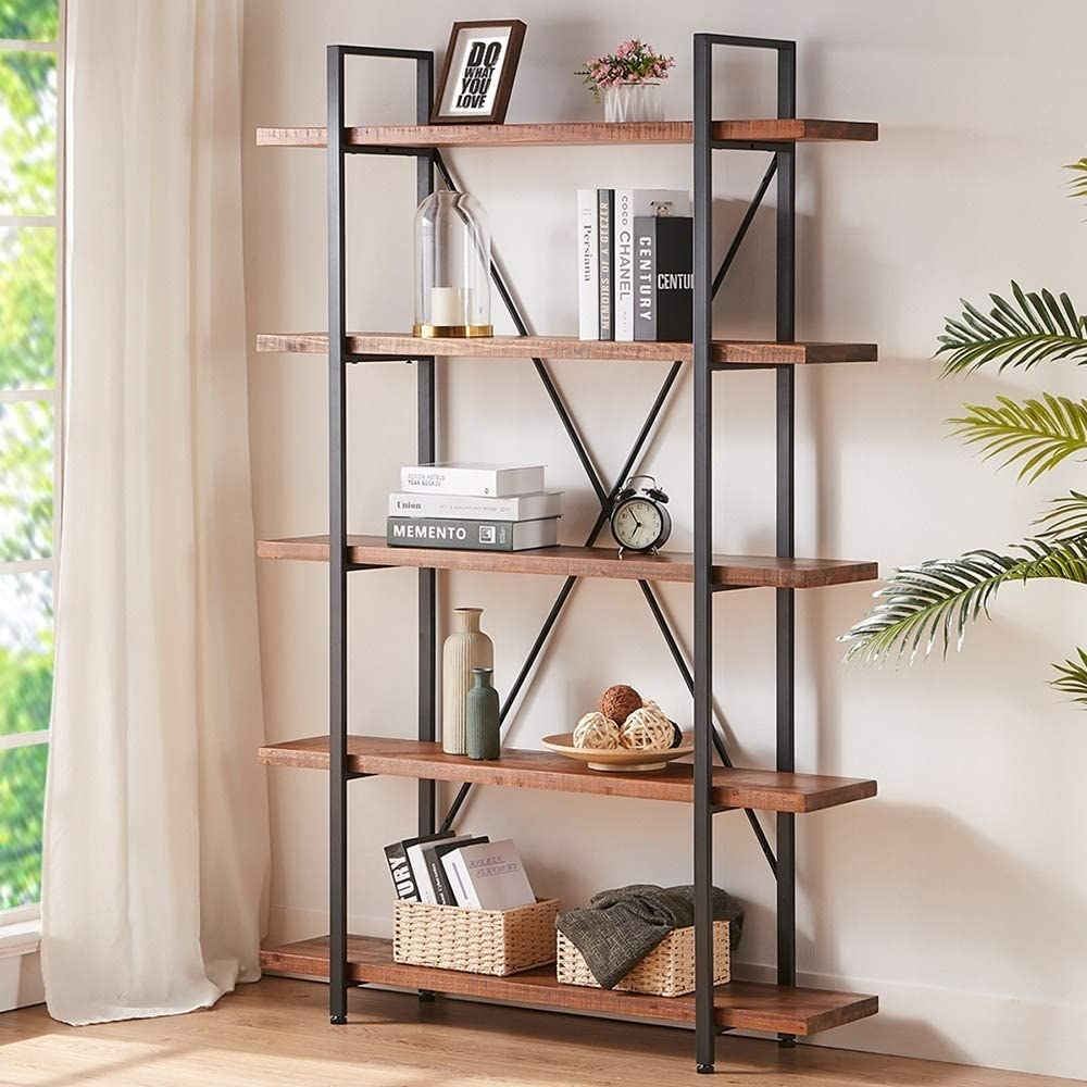 the bookcase with long wooden shelves and metal pole accents