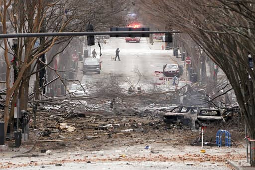 Debris from an exploded RV, including burned-out cars and fallen tree limbs, litters a snowy street