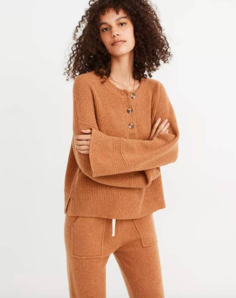 model wearing boxy top with bell sleeves and vents on the side at the bottom with three tortoiseshell oversize buttons at the neckline