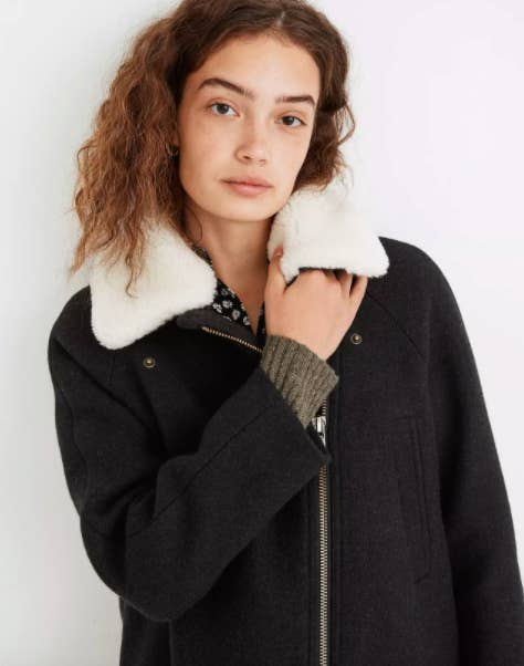Model wearing heavy navy coat with zip up and sherpa collar