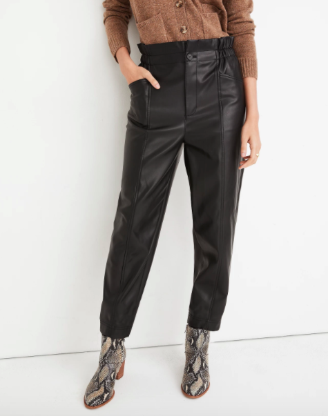 model wearing slack-like fit faux leather pull on pants with a sweater and snakeskin print boots