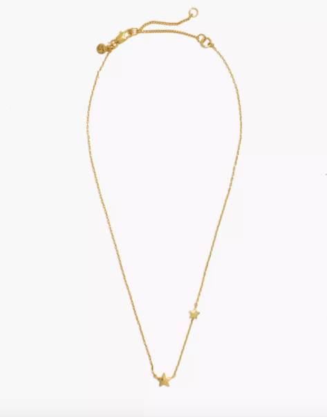 gold tone necklace with two star charms on it