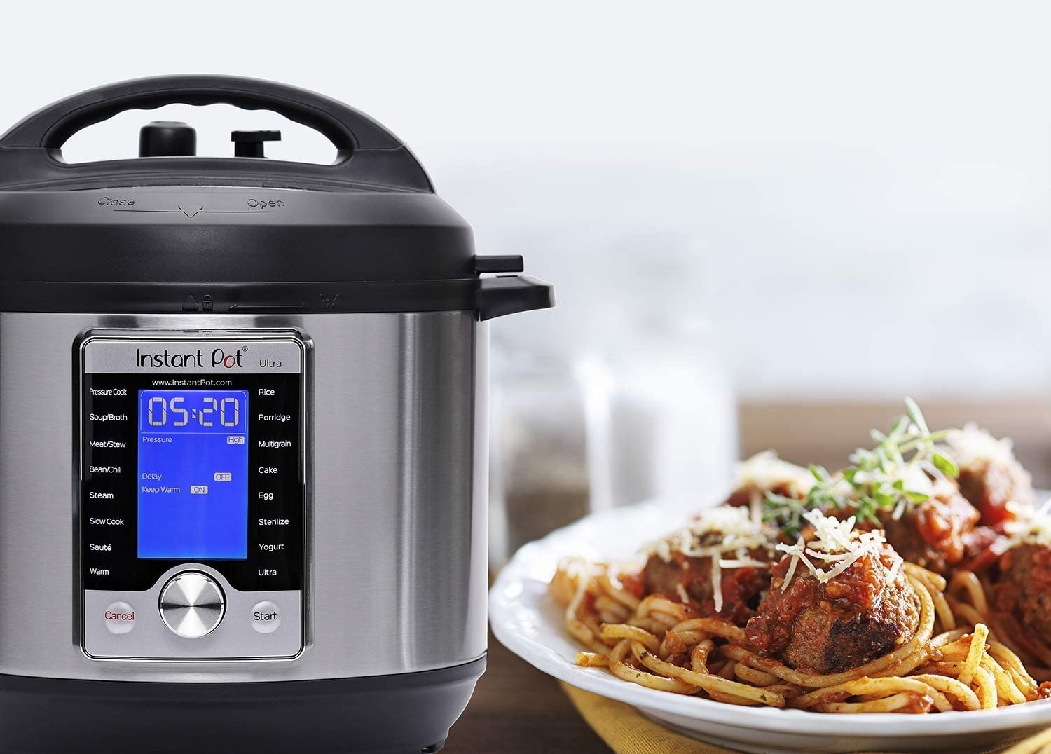 An Instant Pot next to a bowl of spaghetti and meatballs