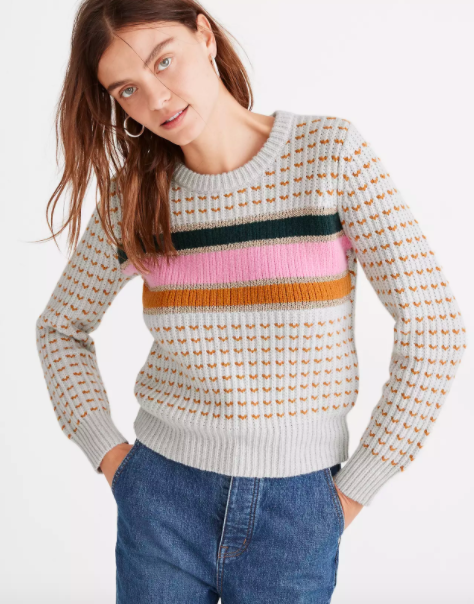 model wearing light gray crewneck sweater with pink black and orange stripes across chest