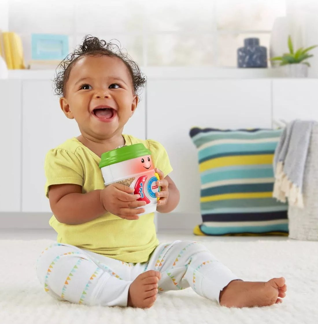 A baby playing with the coffee cup toy