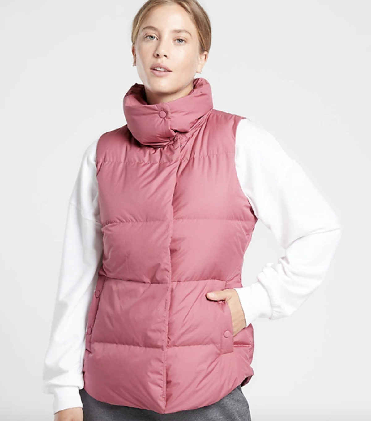 a model wears the eros pink downtown vest layered over a white sweater