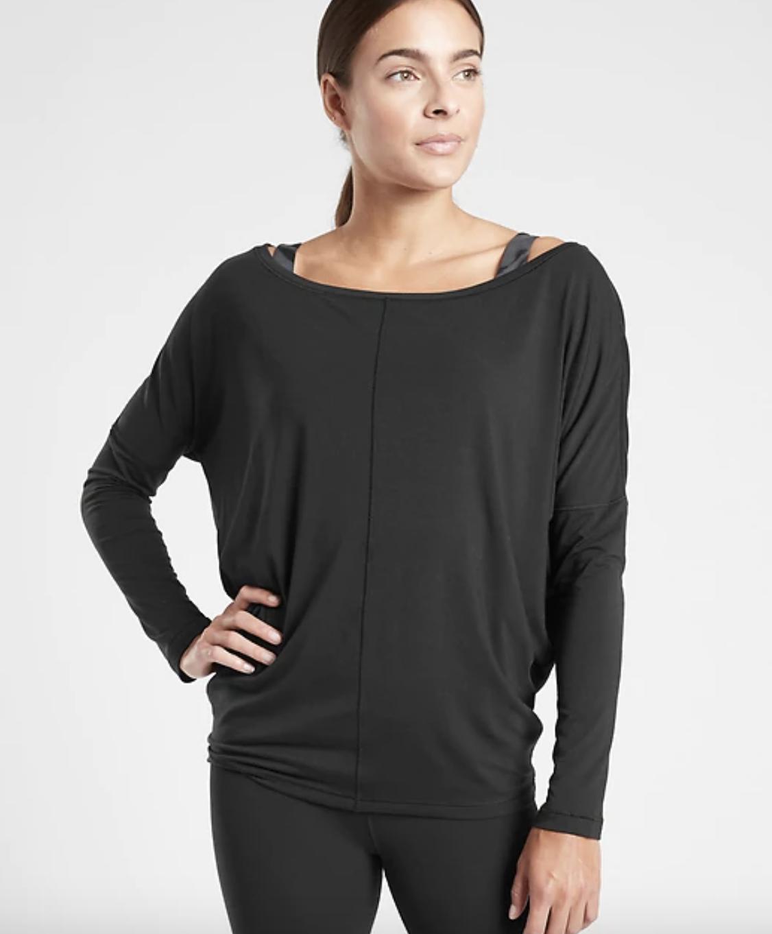 a model wears the black essence flow top