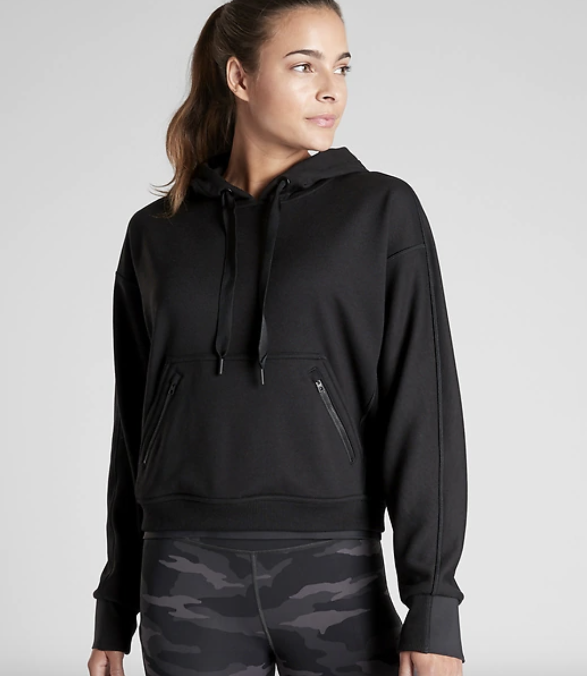 a model wears the black recover hoodie