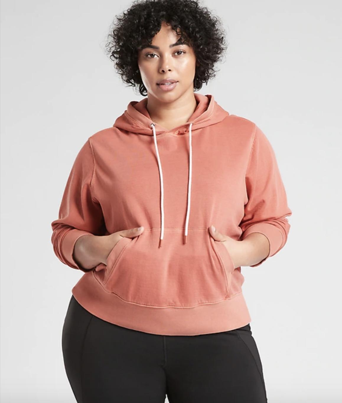 a plus size model wearing the sundown hoodie in etruscan red