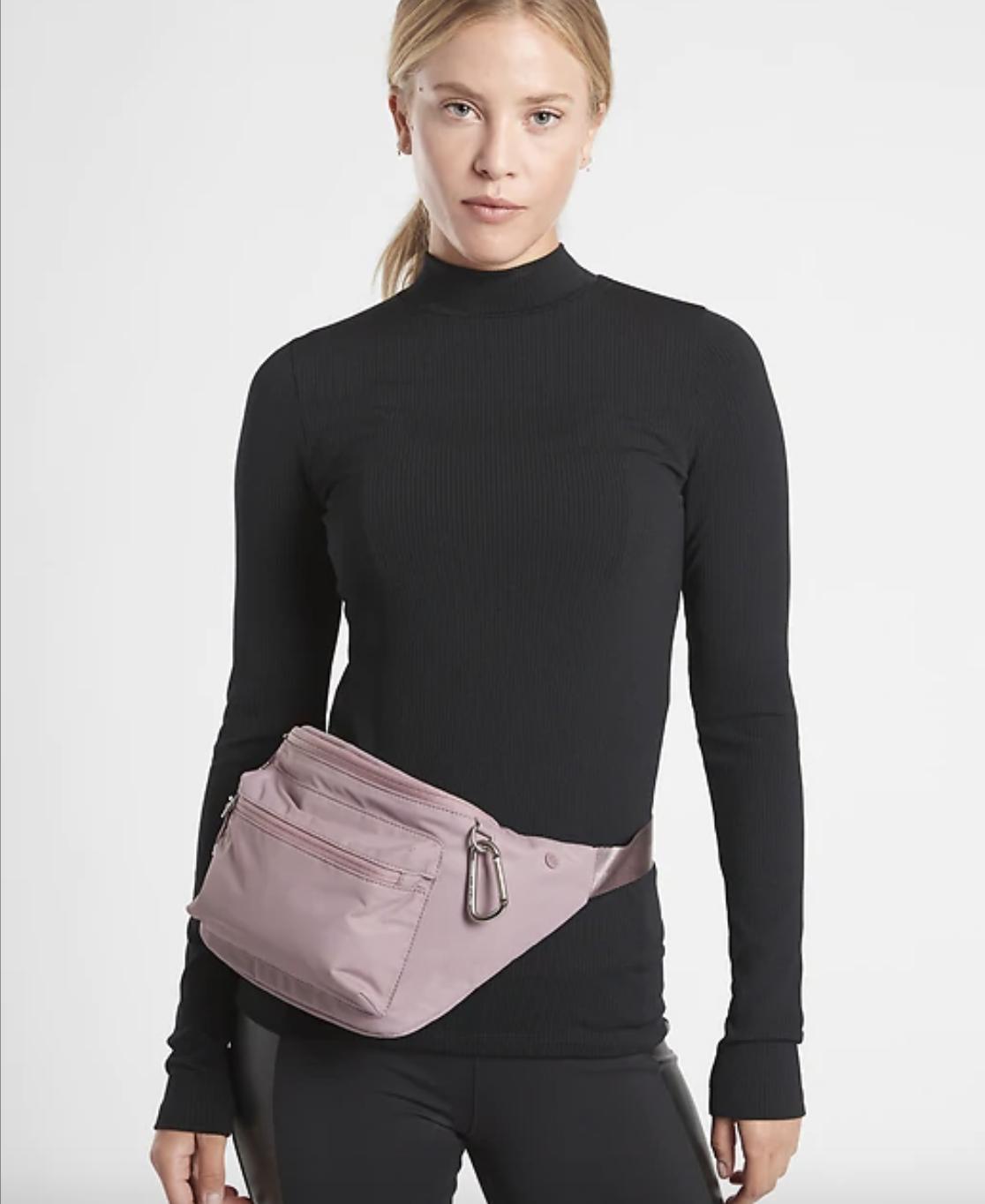 a model wears the flora mauve via waistbag around their waist