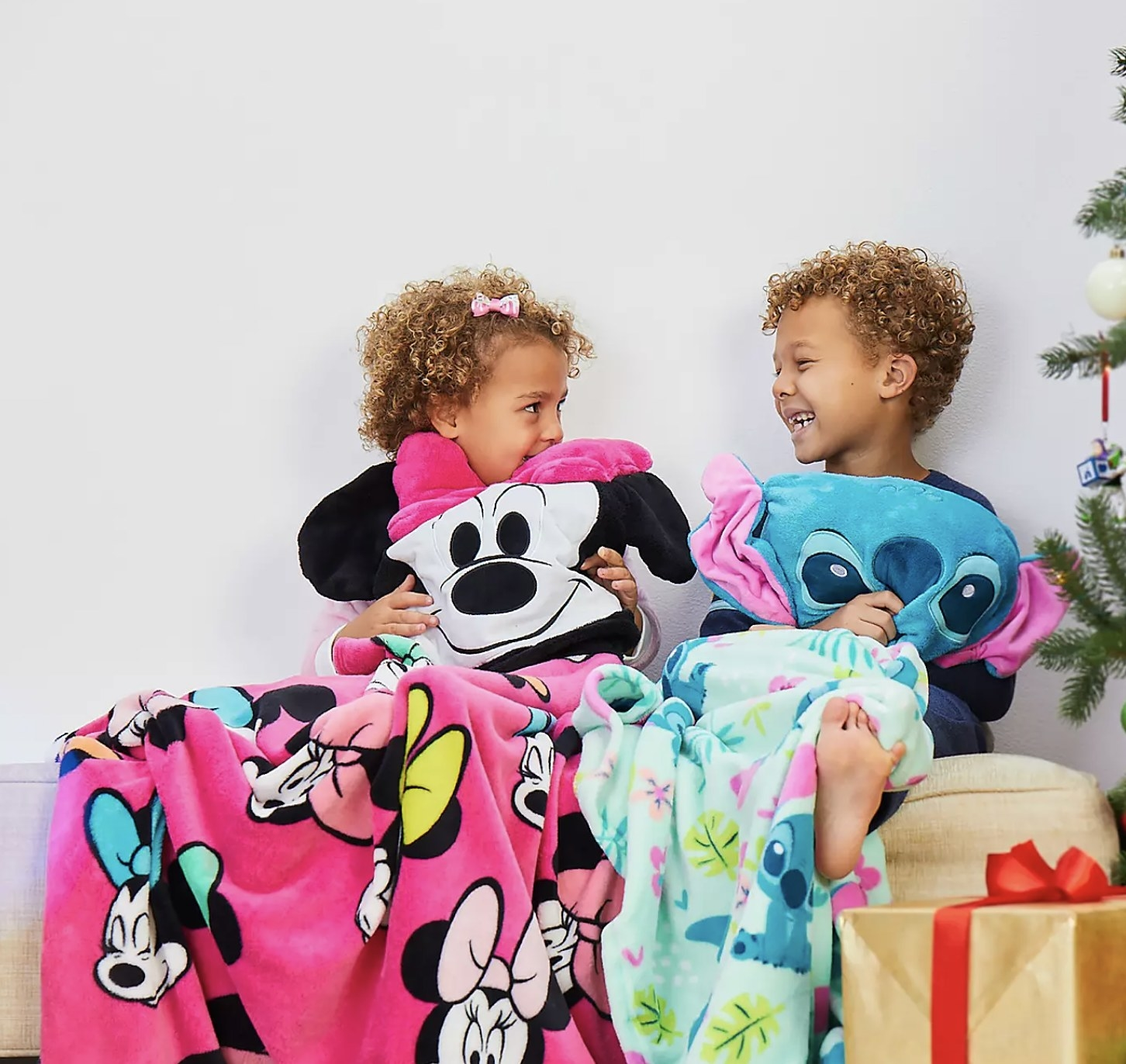 Two people in throw blankets of Stitch and Minnie Mouse