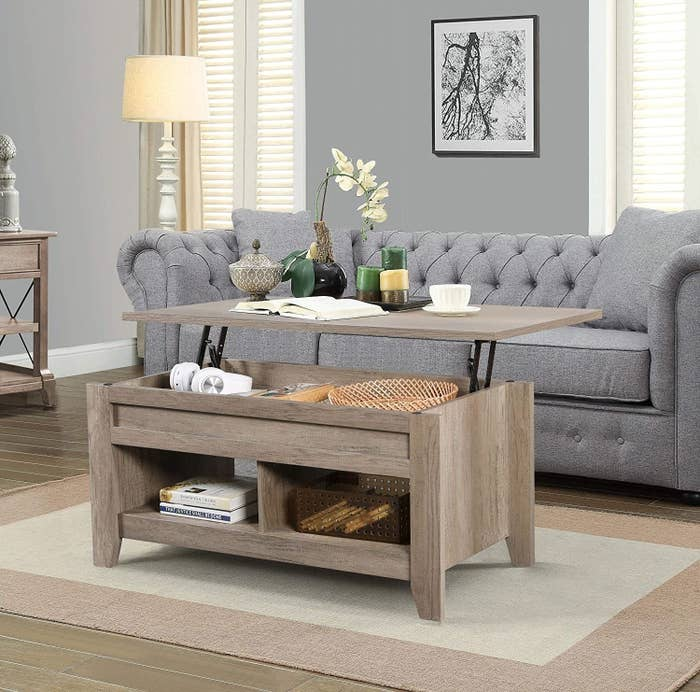 the light wood coffee table with the top lifted to show the storage inside