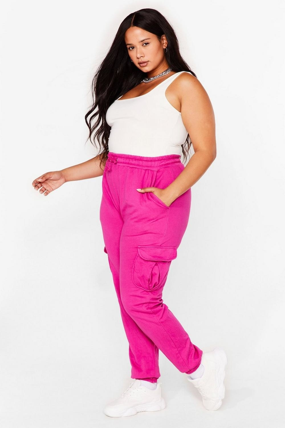 Model wearing the hot pink sweatpants with pockets on the side and thighs