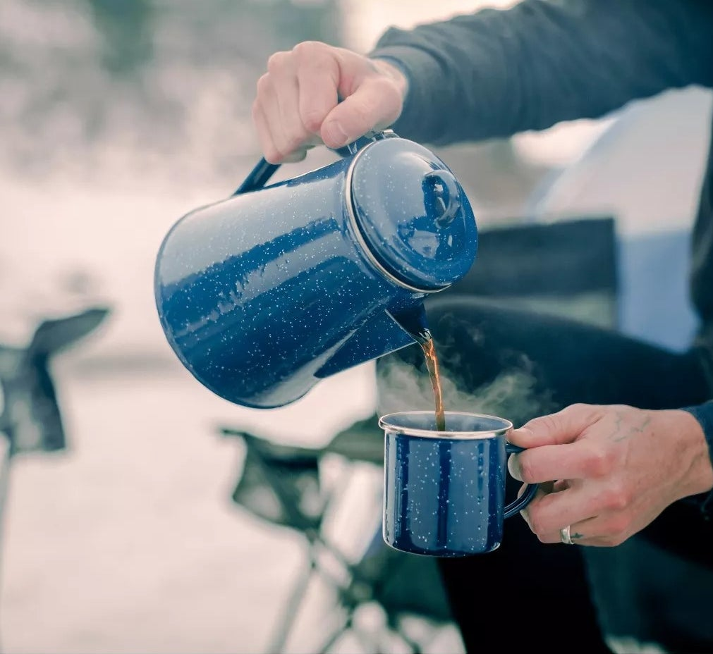 A hand pouring a cup of coffee using the pot