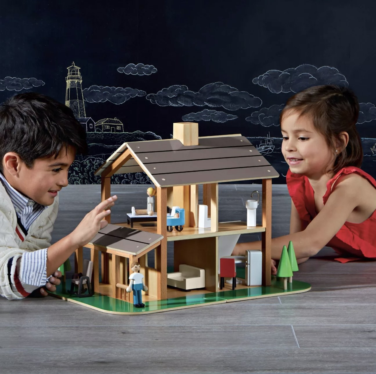 Two people playing with a wooden dollhouse