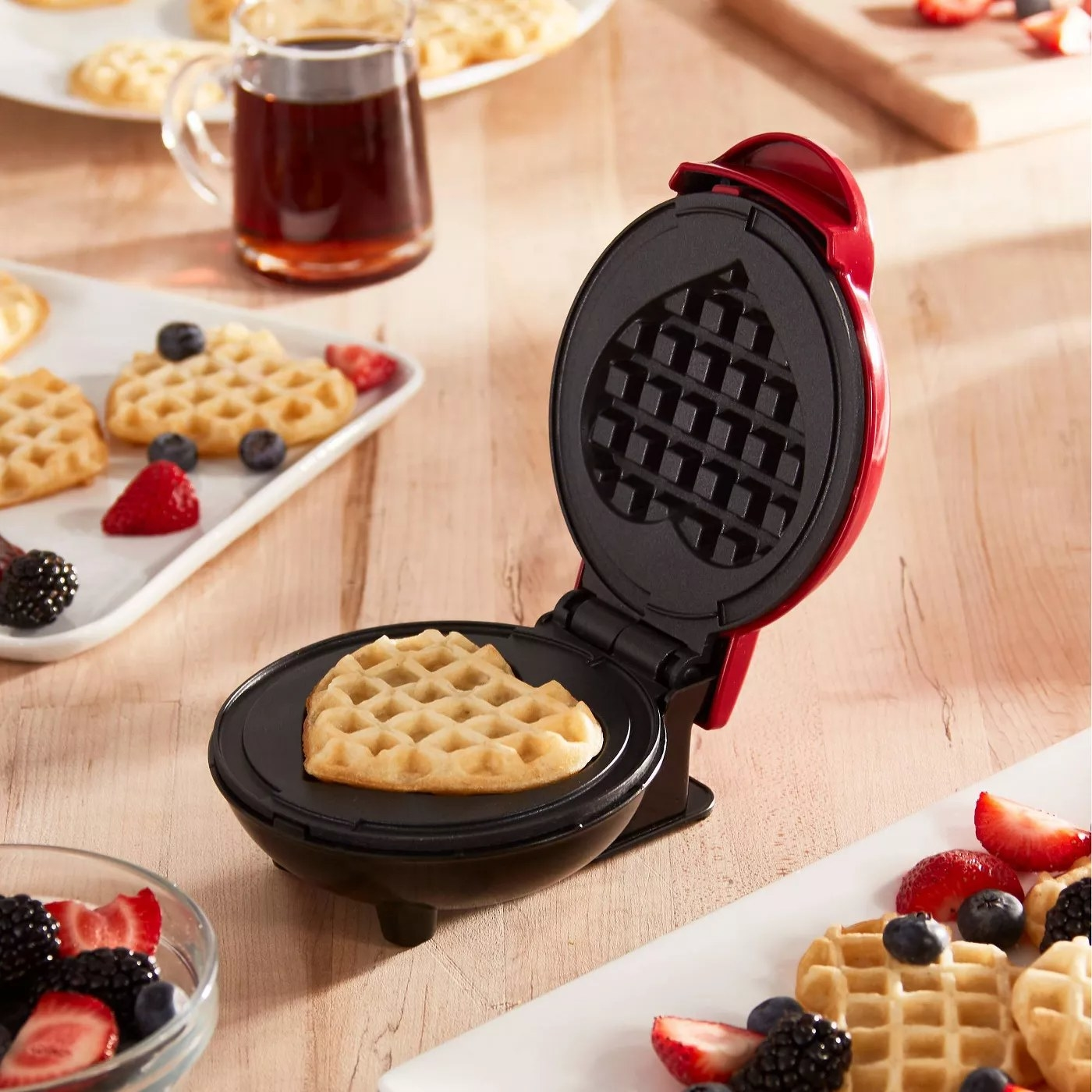 The same waffle maker in use, opened, revealing a heart-shaped waffle inside