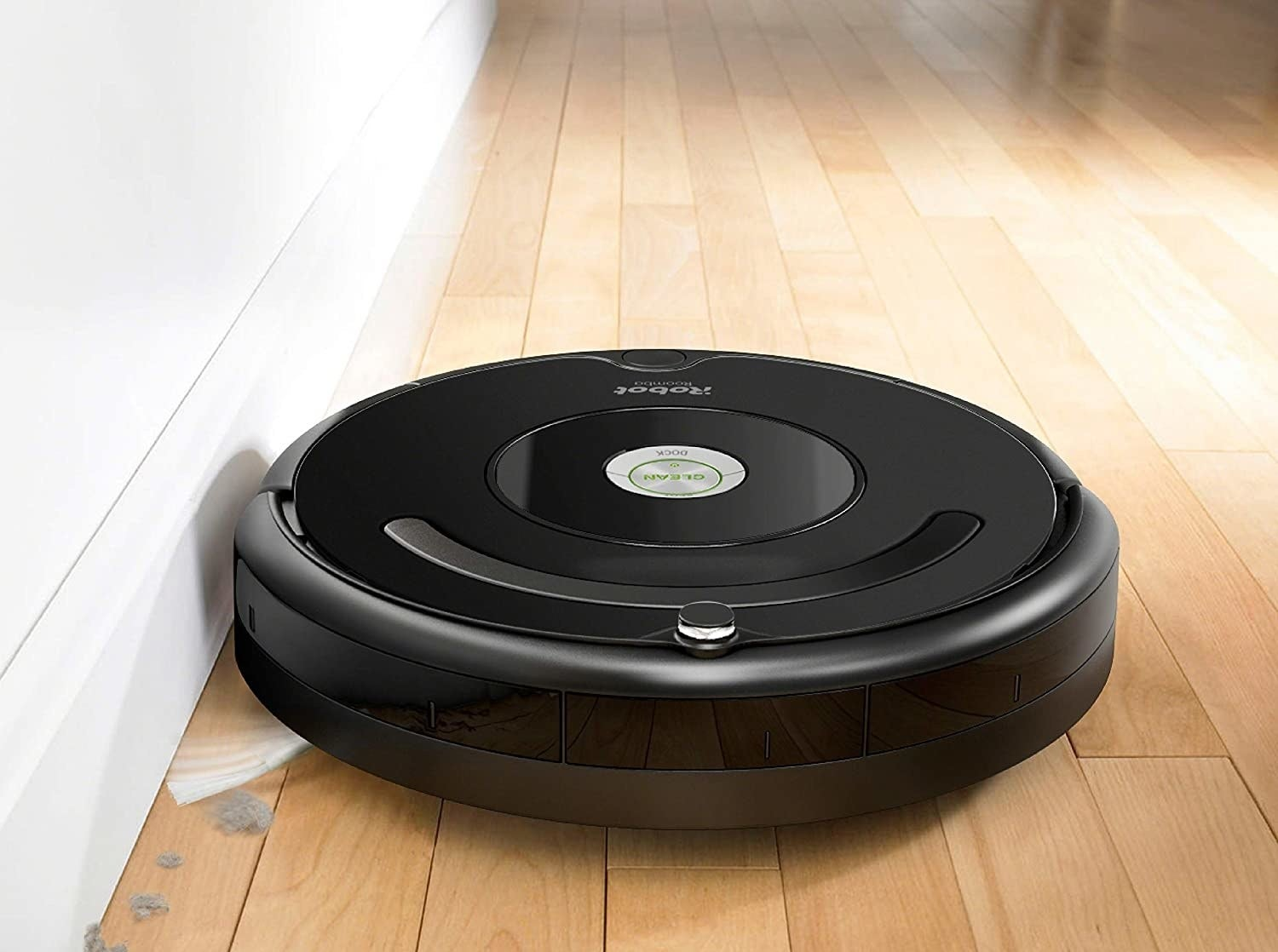 A small round vacuum cleaner sweeping up dust along a wall