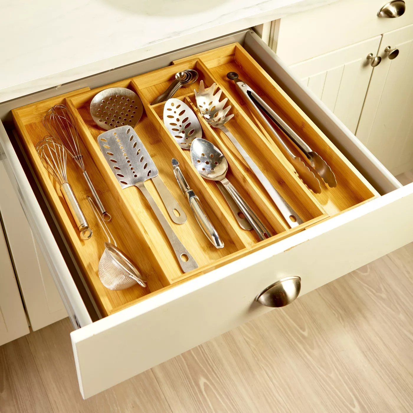 The tray in an opened drawer with kitchen utensils inside