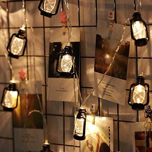 Lantern lights hung on a wall above various photos.