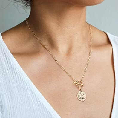 person wearing gold tone necklace with paperclip chain with star and moon medallion
