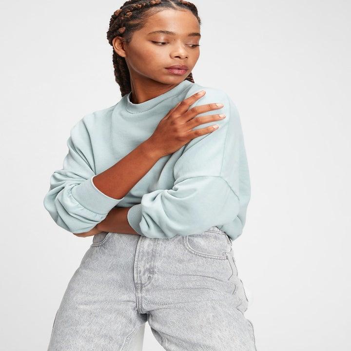 a model in an ice blue sweatshirt
