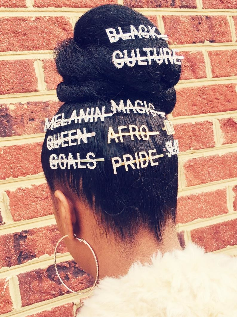 the back of black woman with an updo and several silver and gold statement pieces in her hair