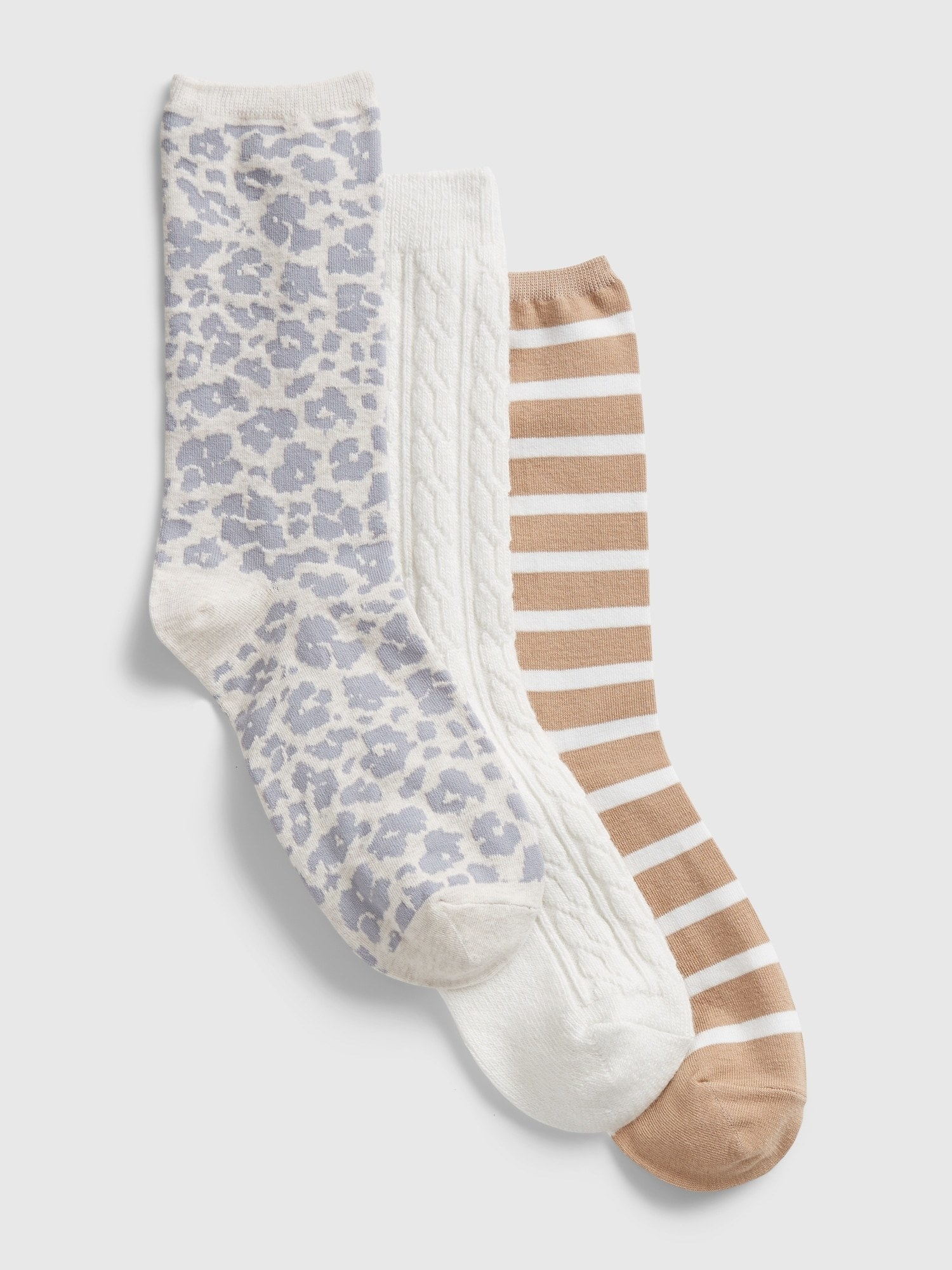 three pairs of socks, one white with gray leopard print, one white and knit, and one camel with white vertical stripes