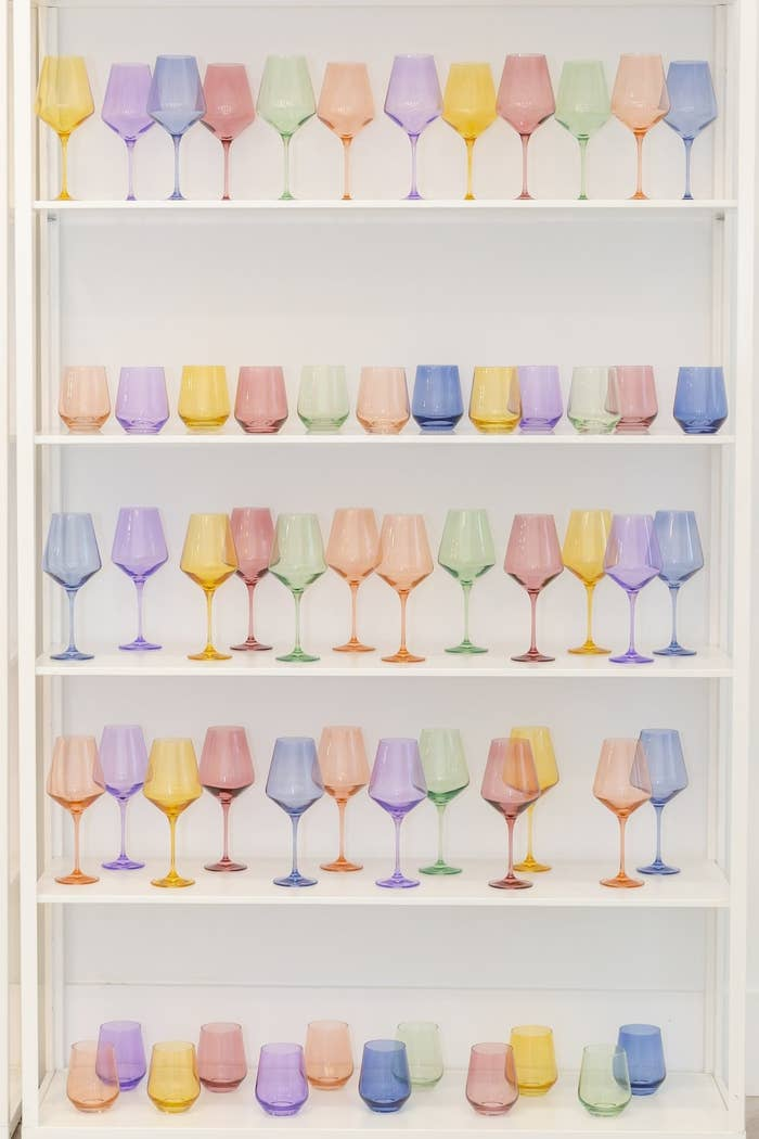 Cabinet holding a mixture of stemmed and stemless wine glasses in a variety of colors