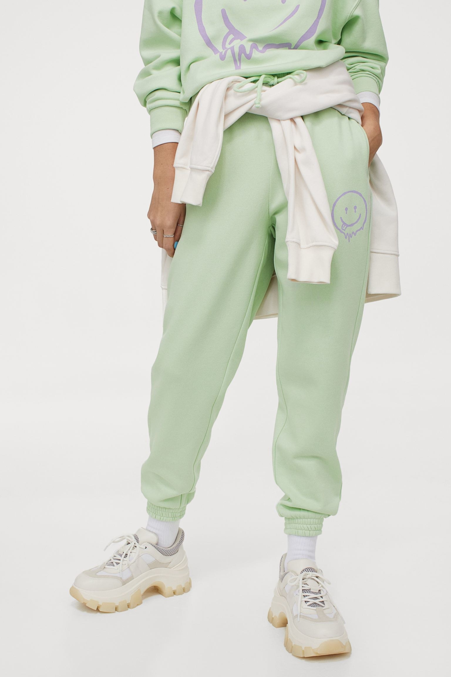Model wearing the mint green sweatpants with a purple smiley face on the side