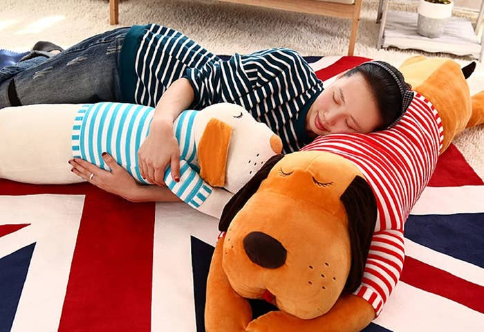 A person sleeping on a dog cushion while cuddling another.