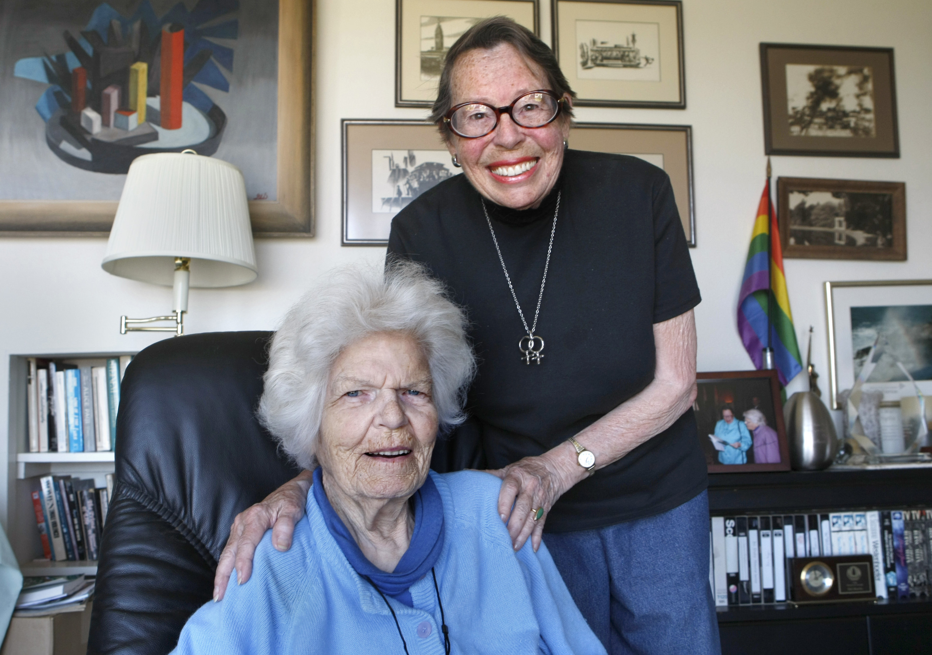 Two older women in their living room with a pride flag in the background