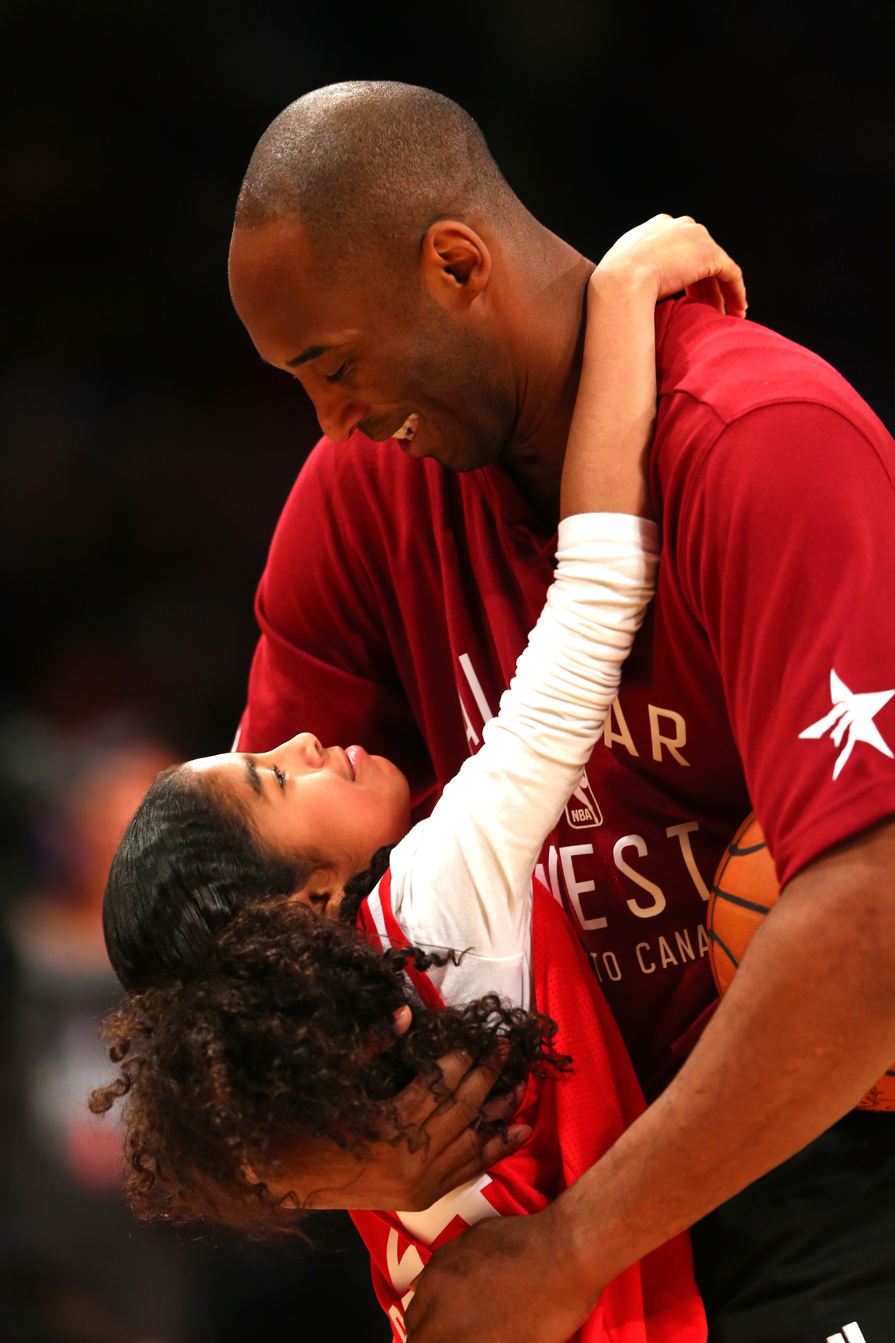 Kobe Bryant holding his daughter Gianna  and laughing with her as she looks up at him