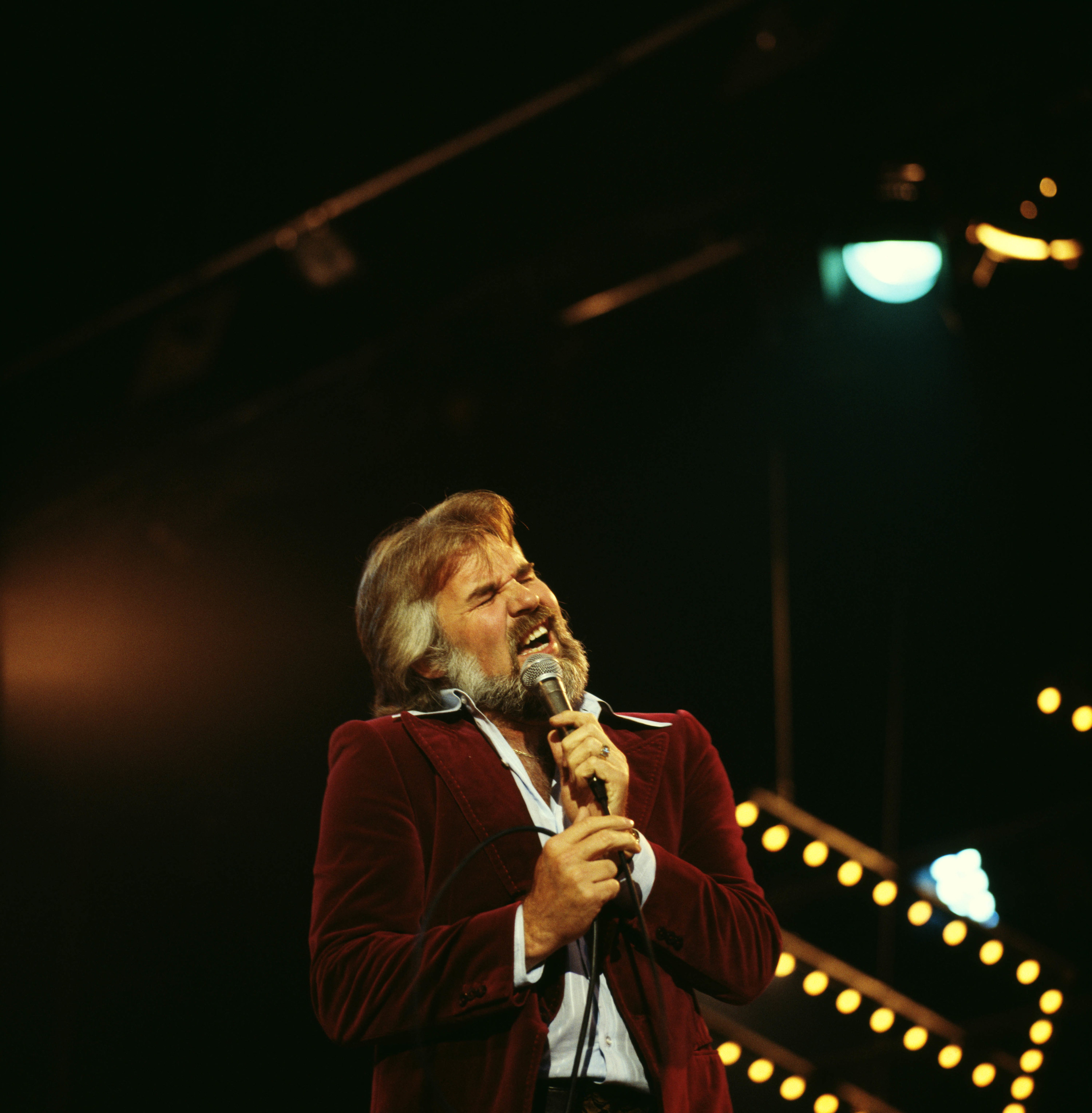 Rogers in a velvet suit singing into a microphone on stage with lights behind him
