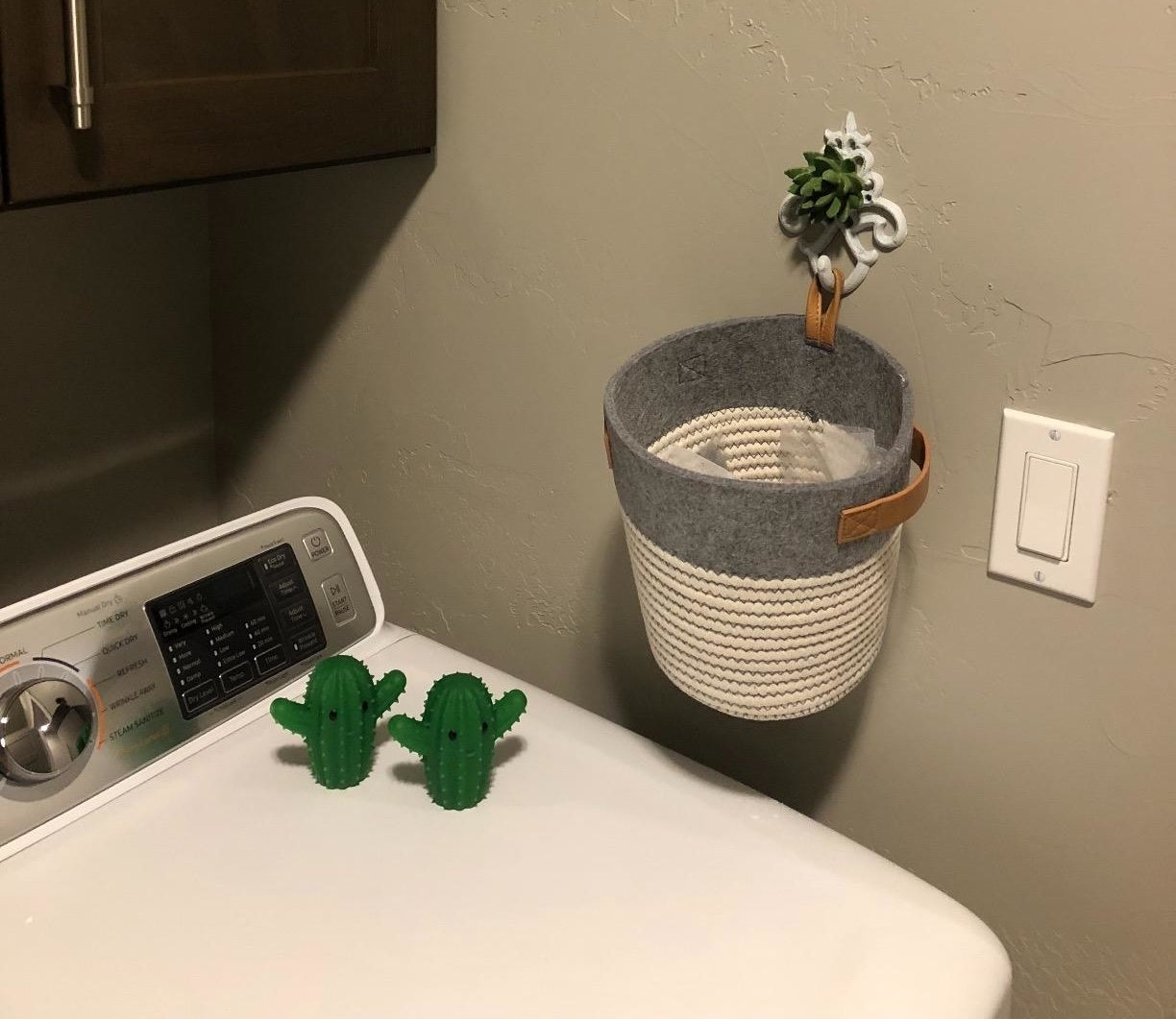 reviewer photo showing two tiny cactus dryer balls resting on top of a dryer