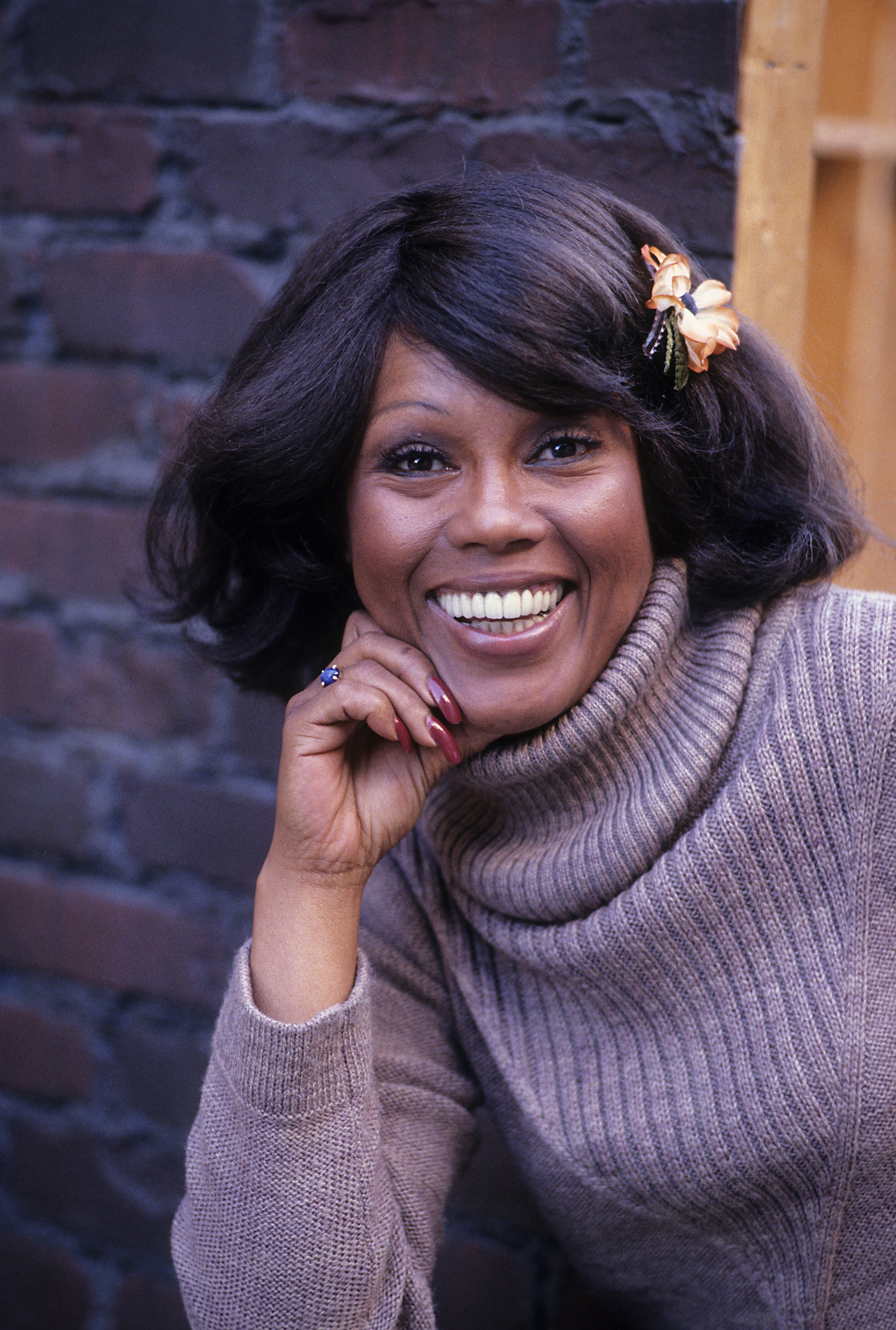 Woman in a purple sweater looking and smiling at camera