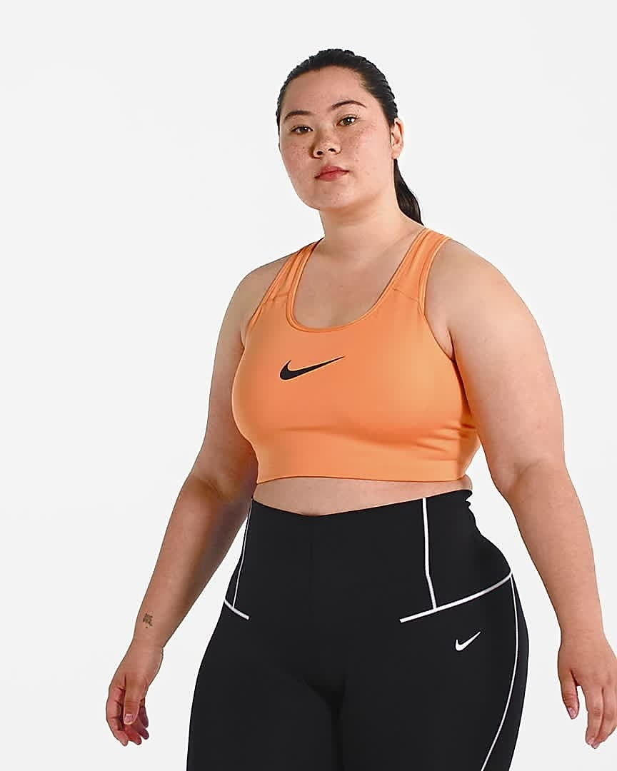 Model wears peach Nike medium-support sports bra with black high-rise leggings