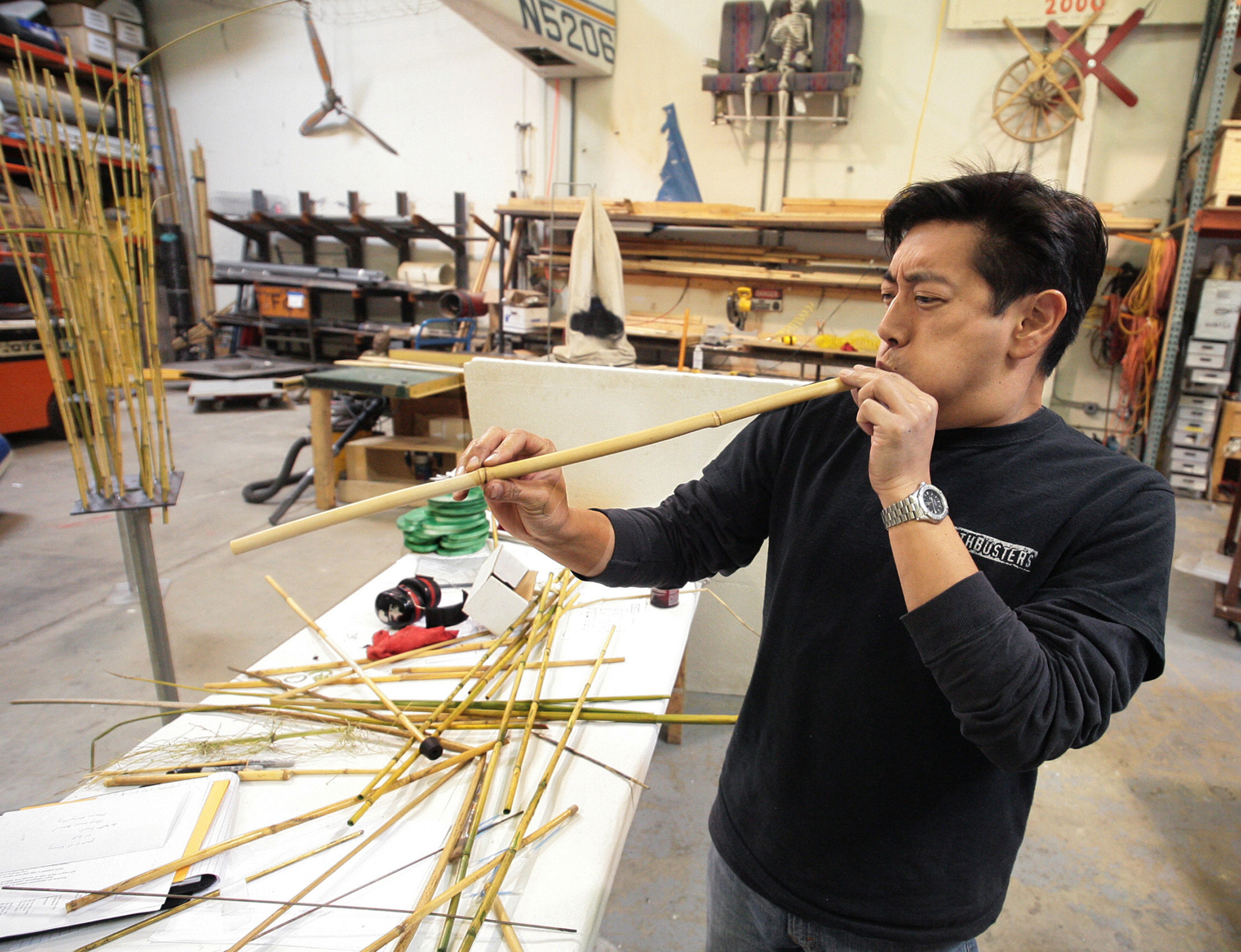 Man testing out a bamboo blowpipe in a workshop