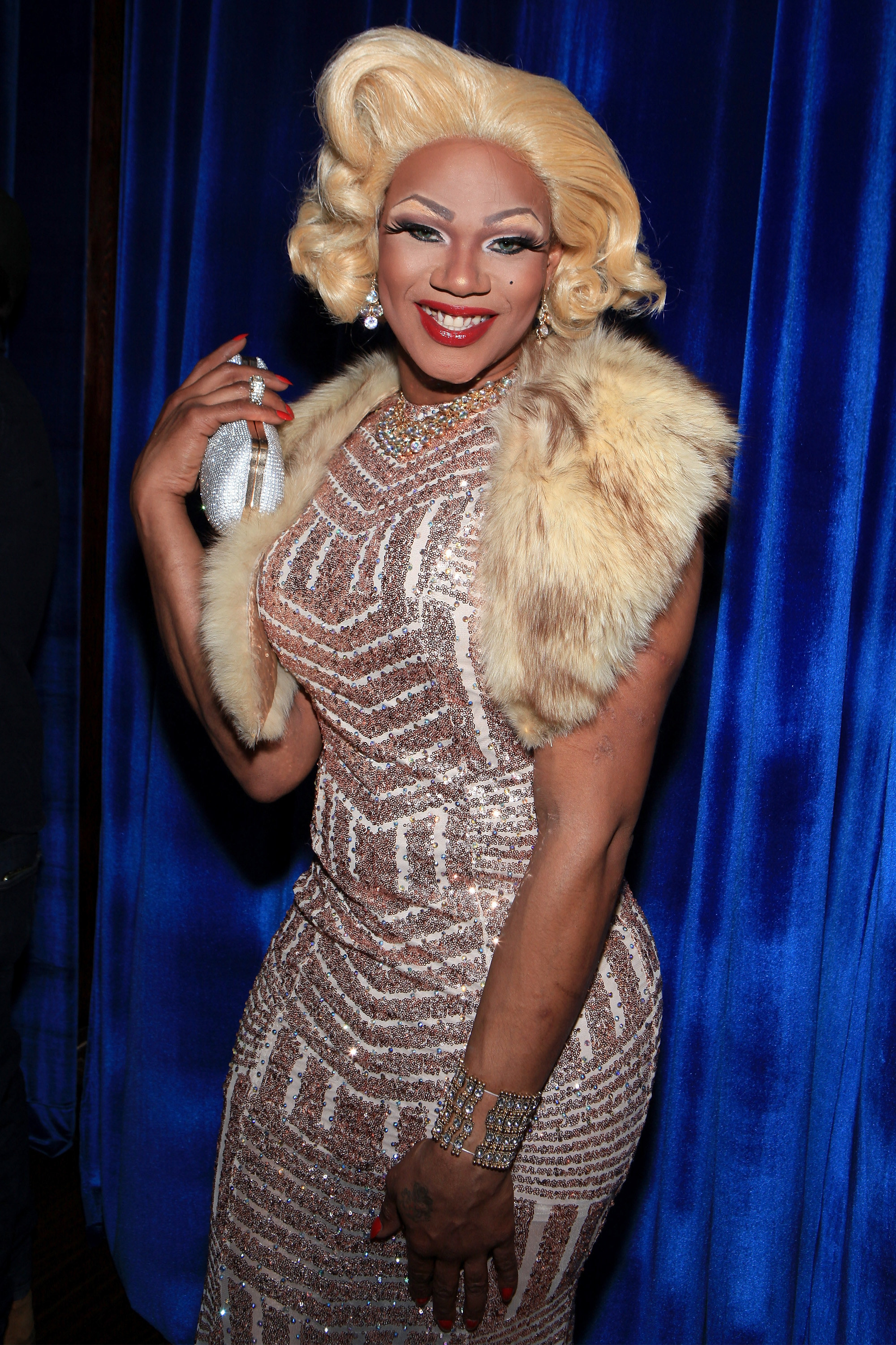 Chi Chi DeVayne smiling at the camera in a sparkly dress and with full makeup