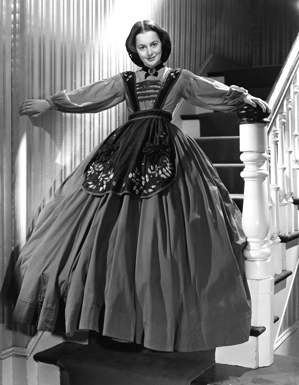 De Havilland in a full dress on a staircase