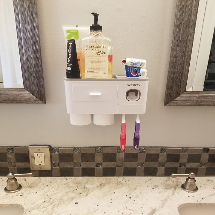 Reviewer using shelf in bathroom to hold products and toothpaste
