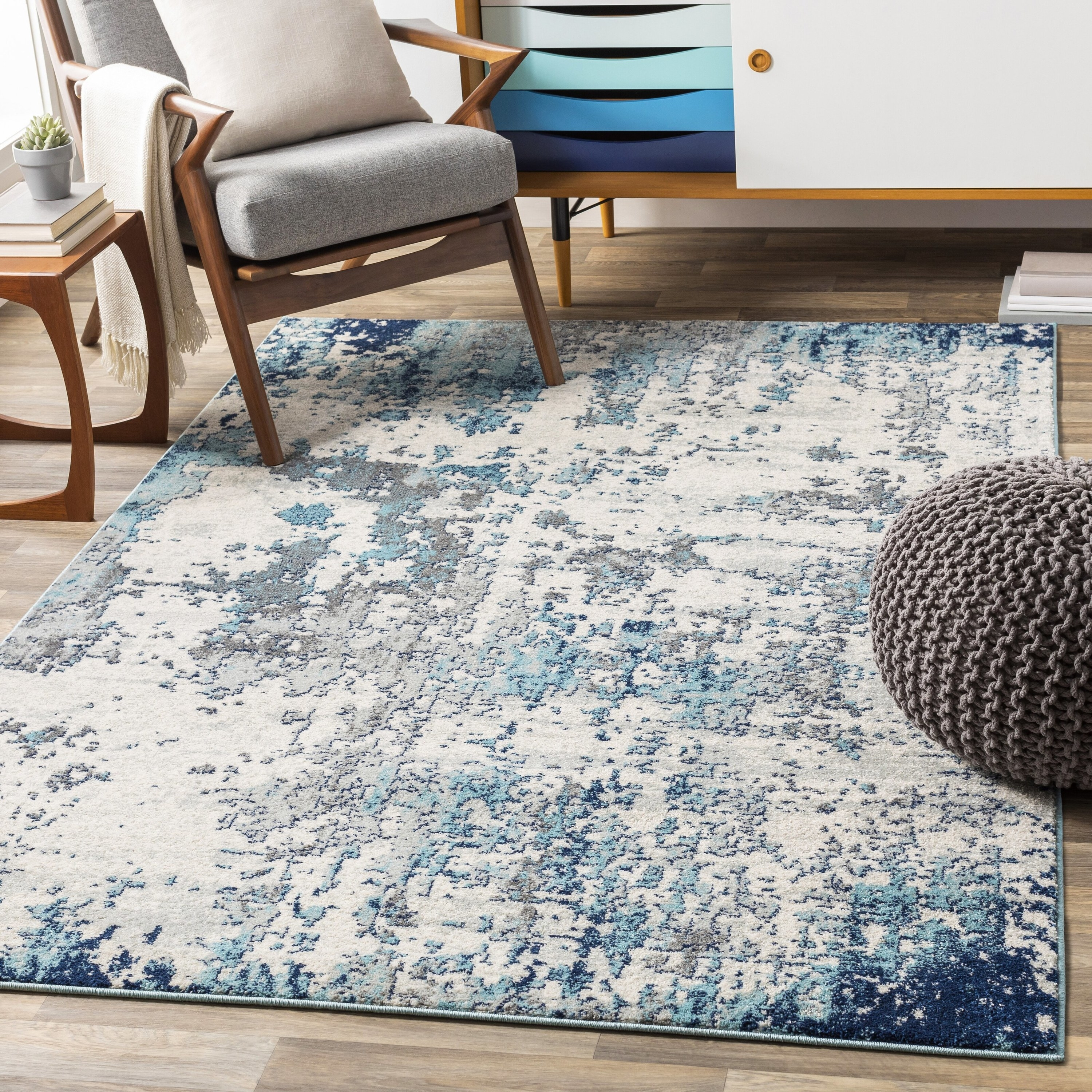 A blue and beige rug with accent chairs and an ottoman around it