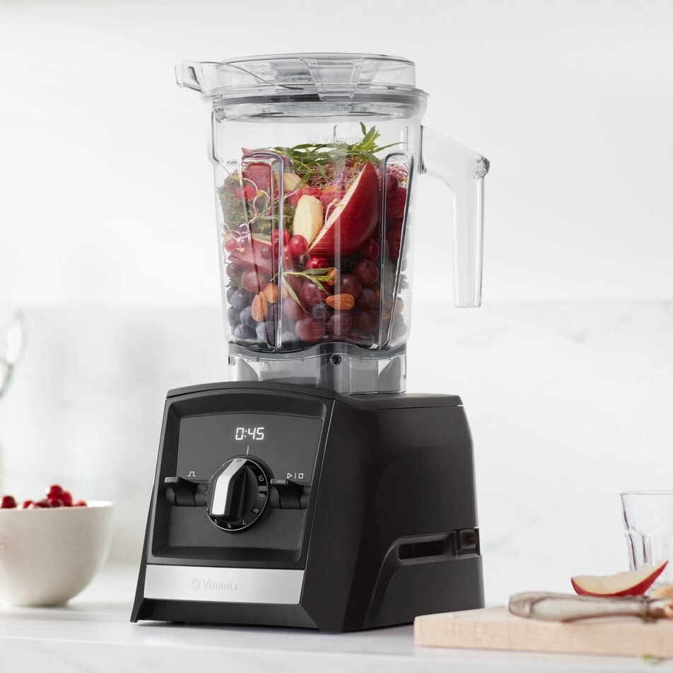 A black blender with fruits inside on a kitchen counter