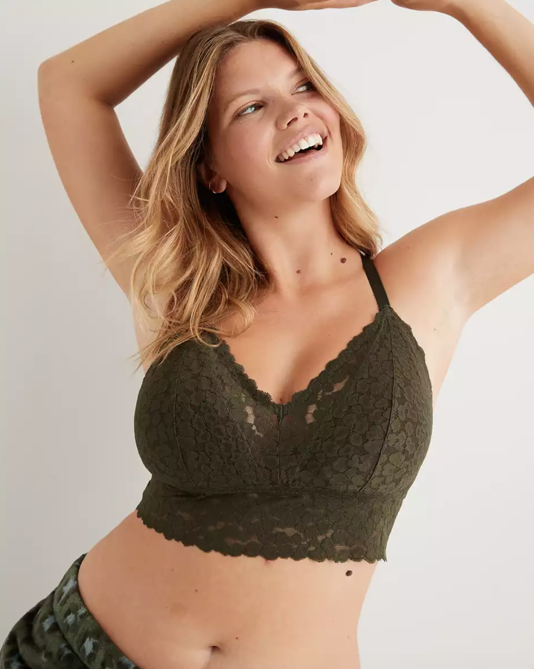a model in an olive green lace bralette