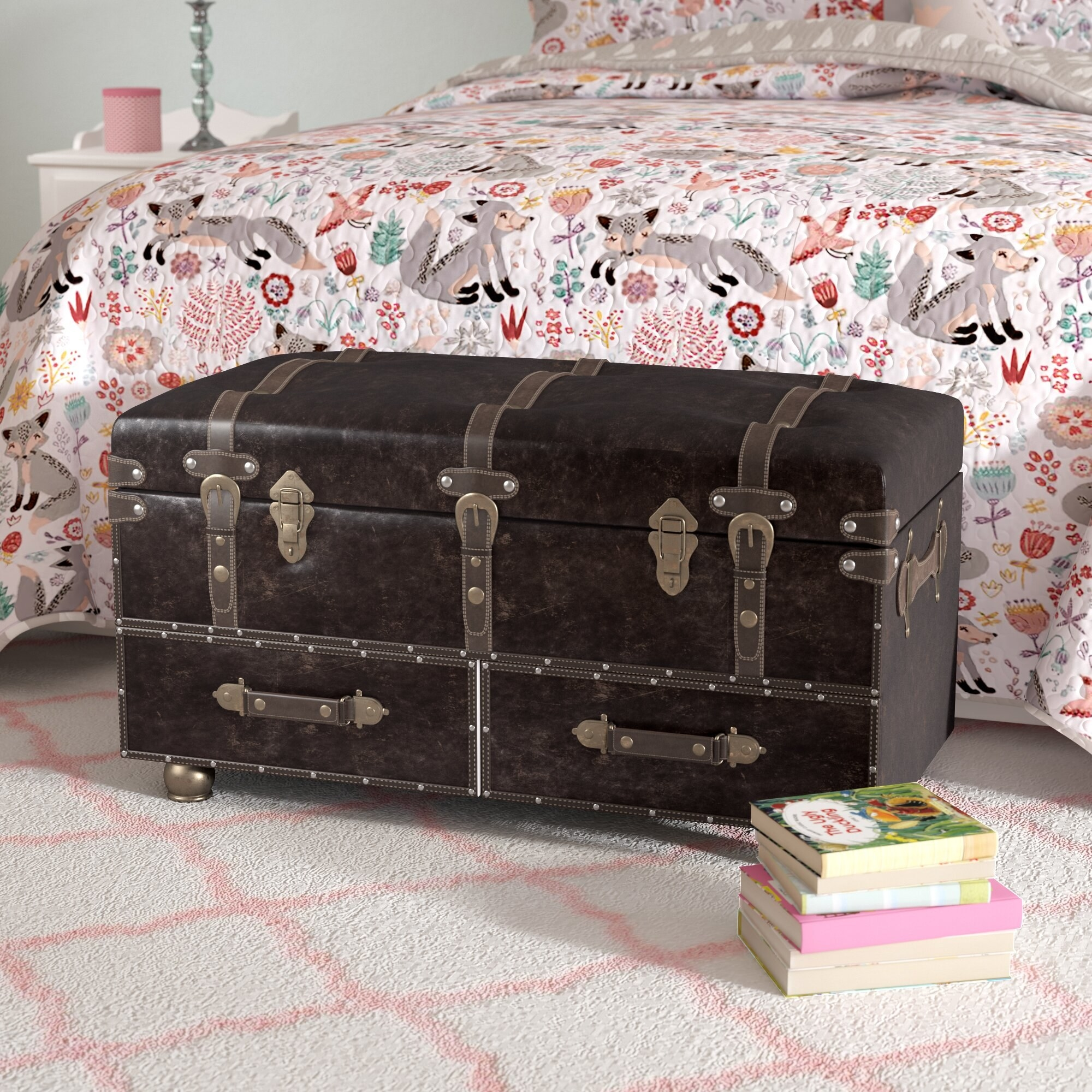 A black leather chest in front of a bed on a rug next to books