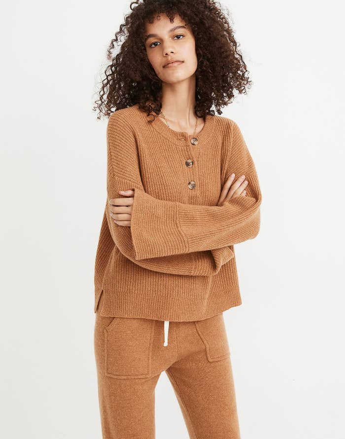 a model in a camel colored sweater with wide sleeves