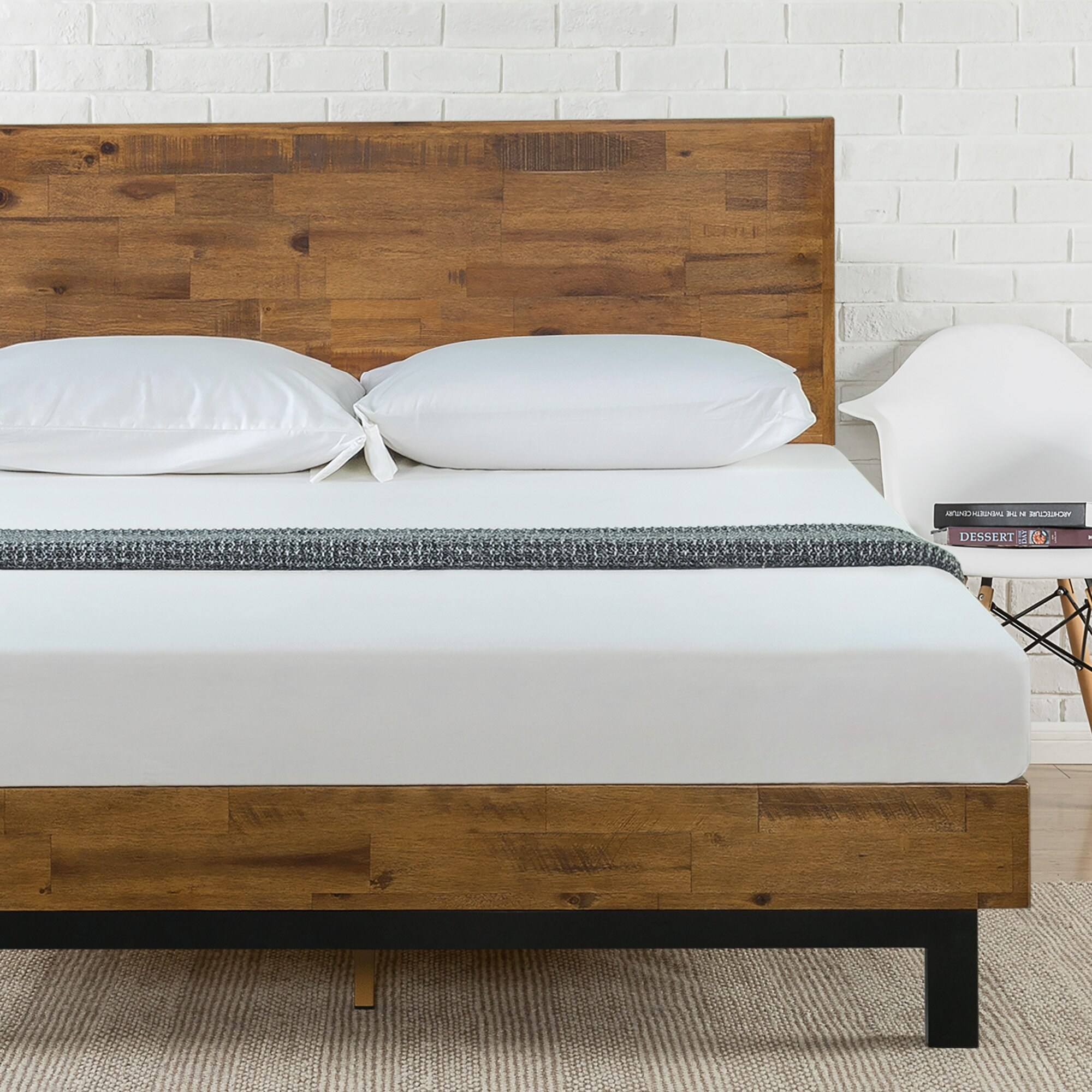 A wooden platform bed with a white mattress and white pillows