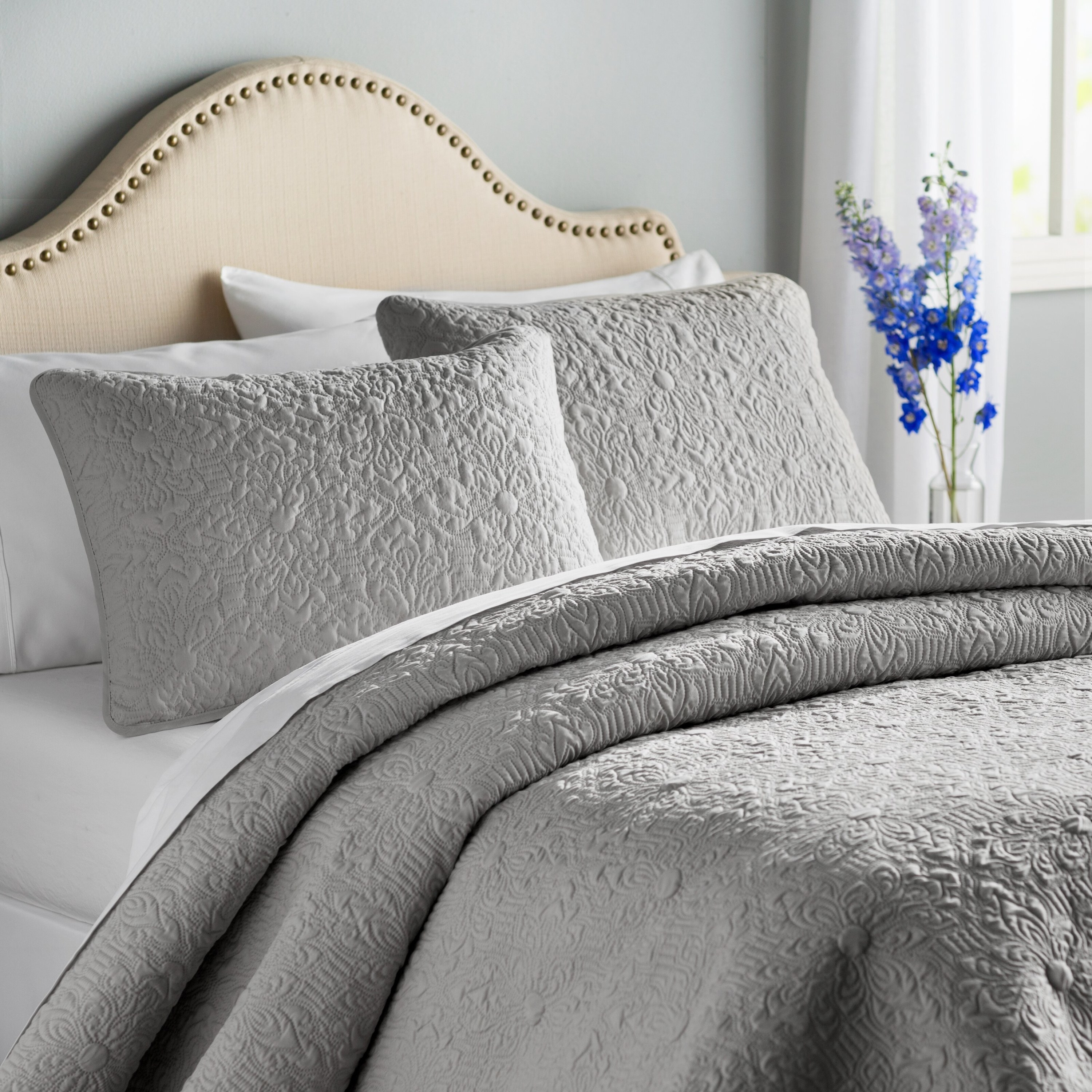 A gray quilted comforter with matching pillow shams set up on a bed with white sheets